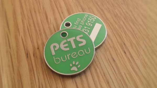 ID Tag from Pets Bureau on a hard wooden surface.